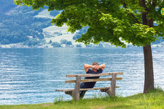 Man resting. On a bench by the lake, Austria Stock Photography