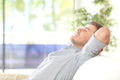 Man resting and breathing at home. Side view of a happy attractive man resting and breathing sitting on a couch at home with a window with a green background royalty free stock photo