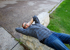 Man resting on a cement bench Stock Image
