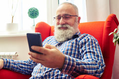 Man resting on the chair with smartphone at home Royalty Free Stock Photos