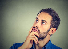 Man resting chin on hand thinking daydreaming, staring thoughtfully upwards Stock Photography