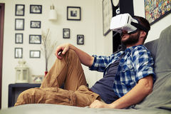 Man resting on comfortable sofa wearing VR headset glasses Stock Photo
