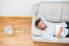 Man resting on couch with writer block Royalty Free Stock Photos
