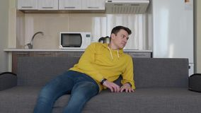 A man is resting on the couch. A young guy reclining sitting and knocks on the sofa. A kitchen on the background. 4K footage stock video footage