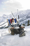 Man Resting On Deckchair In Snowy Mountains. Man in warm clothing resting on deckchair in snowy mountains Royalty Free Stock Photography