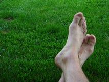 Man resting feet on nice green grass crossed. Feet on green grass crossed,and relaxing Stock Photos