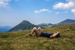 Man resting on the grass in the mountains Royalty Free Stock Photography