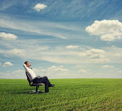 Man resting on the green field Stock Photos