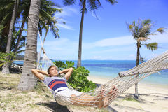 Man resting in a hammock under the palm trees on the beach with white sand and azure sea Stock Image