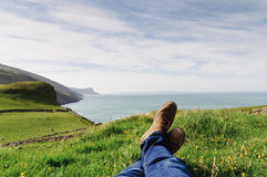 Man resting on the hill. Man laying on the ground in a grass field, resting on a hill in the County Antrim, Northern Ireland stock photo