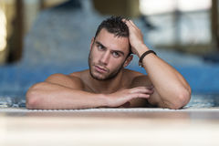 Man Resting His Arms At Edge Of Pool Royalty Free Stock Image