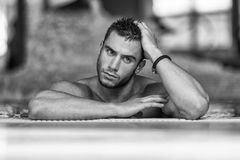 Man Resting His Arms At Edge Of Pool Stock Image