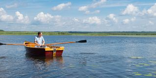 Man resting on the lake, riding a boat with oars, there is a place for the inscription stock photo