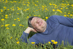 The man resting on the lawn among dandelions Royalty Free Stock Photo