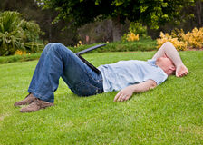 Man resting on lawn with half closed laptop Stock Photography