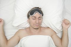 Man resting in a mask for sleep. Stubble on his face. Tired man stock image