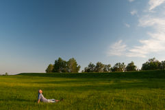 Man resting in the middle of huge meadow Stock Photography