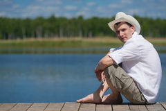 Man resting on nature while sitting on the pier. Young man in a cowboy hat sitting on the beach Royalty Free Stock Photography