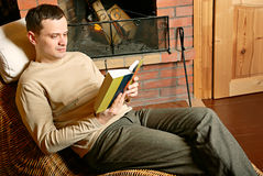 Man resting near fireplace Royalty Free Stock Image