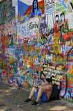 Man resting near the John Lennon Wall, Prague, Czech Republic. Once a normal wall, since the 1980s it has been filled with John Lennon-inspired graffiti and Royalty Free Stock Image