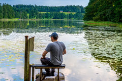 Man resting near lake. In summer Stock Images