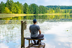 Man resting near lake. In summer Stock Photography