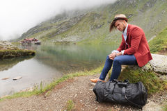 Man is resting near a mountain lake with cabin Stock Photos