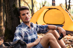Man resting near tent in the forest Stock Photos