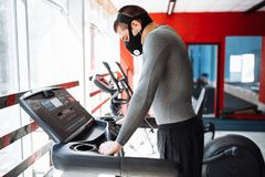 Man resting before the next race, doing sports, in a training mask for breathing on the treadmill, morning training royalty free stock photos