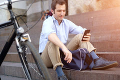 Man is resting next to his bike and using phone Royalty Free Stock Photos