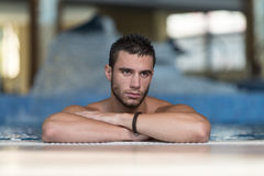 Man Resting Relaxed On Edge Of Swimming Pool Royalty Free Stock Photos