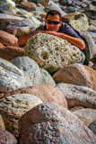 Man resting on rocks. Young man sitting on large boulders on the coastline in northern New Zealand stock images