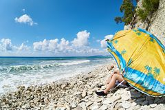 Man resting on rocky beach under umbrella Royalty Free Stock Image