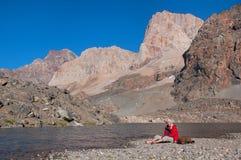 Man resting on the shore majestic mountain lake in Tajikistan Stock Photo
