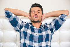 Man resting on the sofa at home. Portrait of a happy man resting on the sofa at home Stock Photography