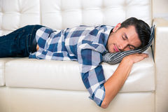 Man resting on the sofa at home. Portrait of a young man resting on cloth in the sofa at home stock photo