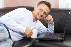 Man resting on sofa and using a computer. Royalty Free Stock Photos
