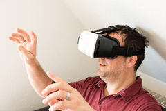 Man resting on sofa wearing VR headset glasses Royalty Free Stock Photos