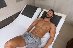 Man Resting On Sun Loungers By Swimming Pool Royalty Free Stock Photo