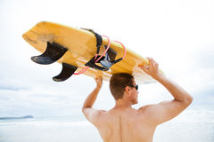 Man resting surfboard on head at beach. Male surfer resting surfboard on head at beach while looking towards ocean and waves Royalty Free Stock Images