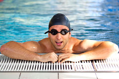 Man resting after swimming. Wearing swimming goggles and cap in deep indoor pool Stock Photo