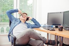Man resting and talking on the mobile phone in the office. Handsome young man programmer talking on the mobile phone, resting and smiling while sitting at his stock images