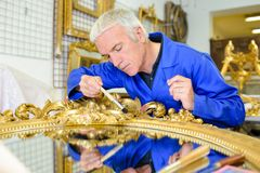 Man restoring gilt mirror. Man stock photography