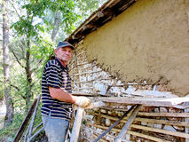 Man restors a house in a traditional manner. A man restors an olde house in a traditional manner. The house was built using natural materials, such as wood, mud Stock Photo
