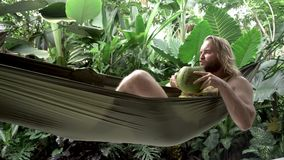 A man rests on a hammock with coconut. In tropical garden stock video footage