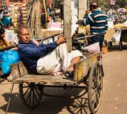 Man rests in his cart in the middle of the day. New Delhi, India, Feb 19, 2018 - Man rests in his cart in the middle of the day Royalty Free Stock Images