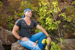 Man rests in the nature sitting on a stone Royalty Free Stock Photos