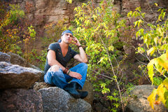 Man rests in the nature sitting on a stone Royalty Free Stock Images