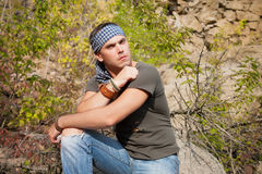Man rests in the nature sitting on a stone Royalty Free Stock Photography