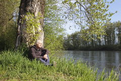Man Rests by River Stock Images